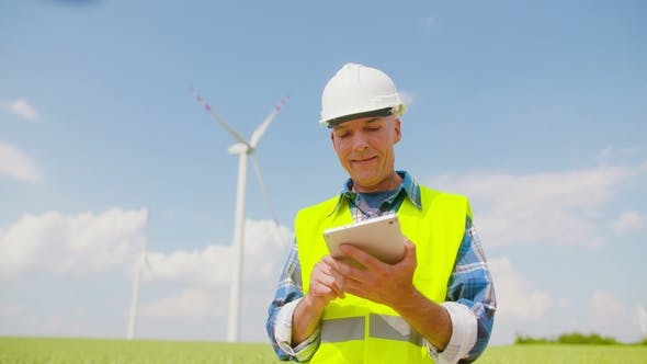 Thumbnail for Engineer Using Digital Tablet on Wind Turbine Farm