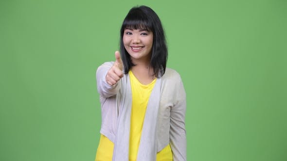 Thumbnail for Beautiful Happy Asian Woman Smiling While Giving Thumbs Up