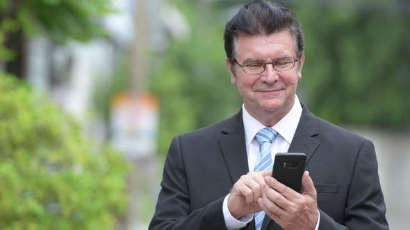 Thumbnail for Happy Handsome Senior Businessman Using Phone in the Streets Outdoors