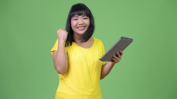 Thumbnail for Beautiful Happy Asian Woman Using Digital Tablet and Getting Good News