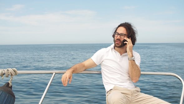 Thumbnail for Young Bearded Man Talking on Smartphone on a Luxury Yacht
