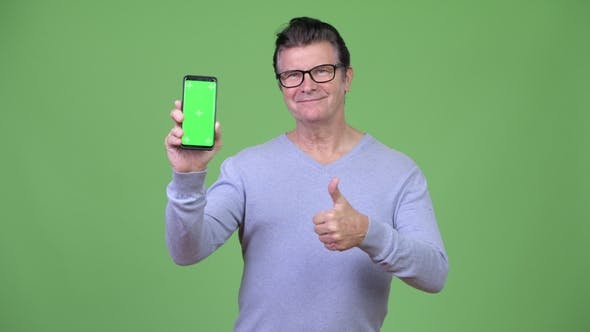 Thumbnail for Senior Handsome Man Showing Phone and Giving Thumbs Up
