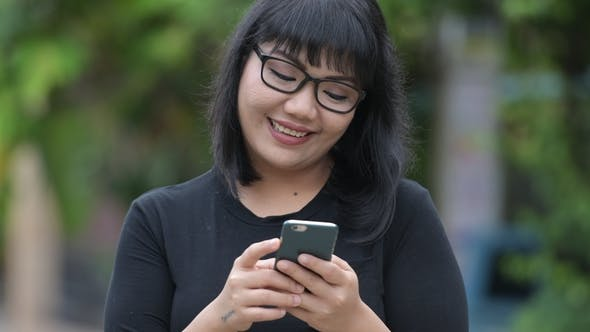 Thumbnail for Beautiful Happy Asian Businesswoman Using Phone in the Streets Outdoors