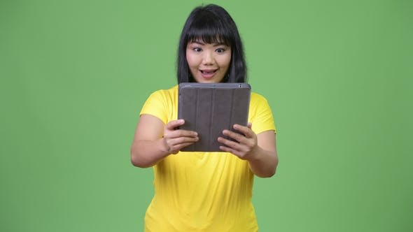 Thumbnail for Beautiful Happy Asian Woman Using Digital Tablet and Looking Surprised