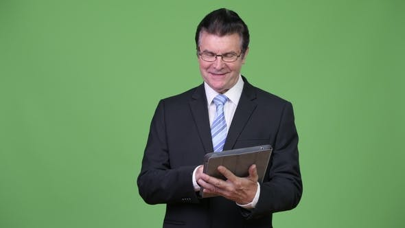 Thumbnail for Senior Handsome Businessman Using Digital Tablet