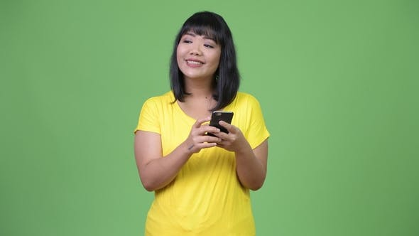 Thumbnail for Beautiful Happy Asian Woman Thinking While Using Phone
