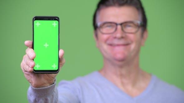 Thumbnail for Senior Handsome Man Showing Phone