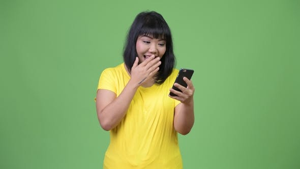 Thumbnail for Beautiful Happy Asian Woman Using Phone While Looking Surprised