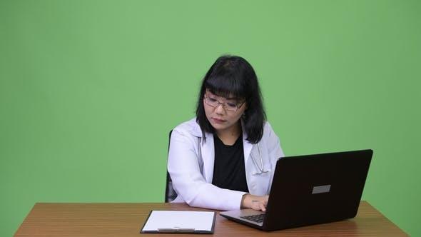 Thumbnail for Beautiful Asian Woman Doctor Multi-tasking at Work