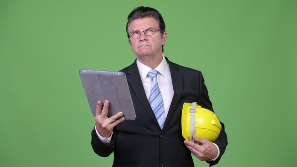 Thumbnail for Senior Handsome Businessman As Engineer Using Digital Tablet