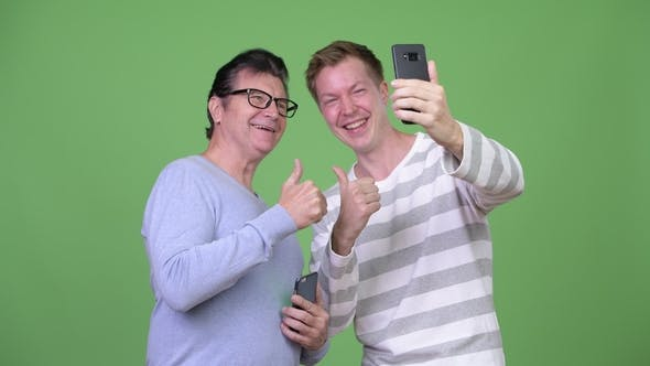 Thumbnail for Senior Handsome Man and Young Handsome Man Taking Selfie Together