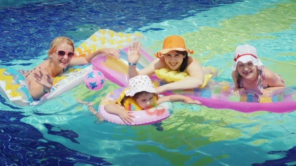 Cover Image for Happy Parents with Children Are Swimming in the Pool. Hold on To an Air Mattress, Look at the Camera