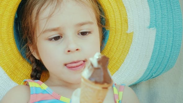 Thumbnail for Portrait of a Cute Little Girl in a Hat. He Eats Chocolate Ice Cream. Summer Vacation with Children