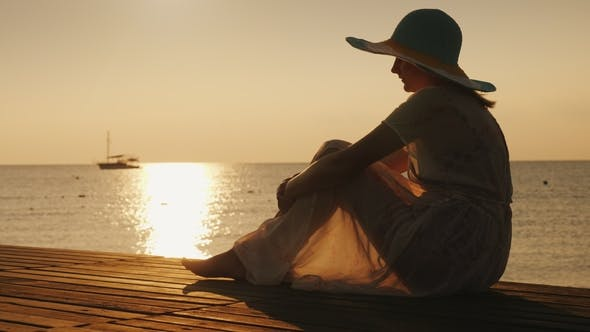 Thumbnail for Side View: A Woman Sits on a Wooden Pier, Meets the Dawn By the Sea. A Ship Is Visible in the