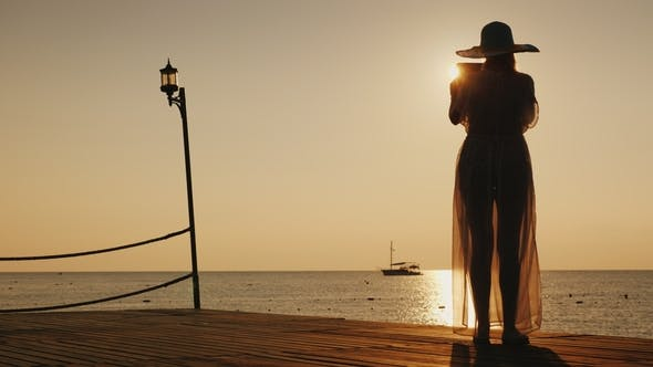Thumbnail for A Young Woman in Beach Clothes Is Standing on the Pier and Is Taking a Photo of a Beautiful Sunrise