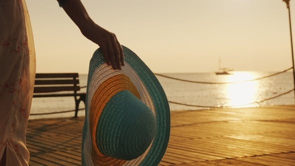 Cover Image for A Woman with a Hat in Her Hand Walks the Pier Towards the Rising Sun. Dream of Travel Concept