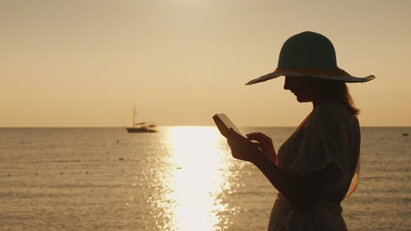 Thumbnail for Silhouettes a Young Woman in a Wide-brimmed Hat That Uses a Tablet Against the Backdrop of a