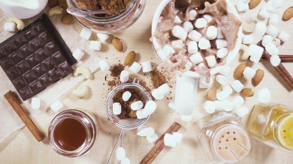 Thumbnail for Auf einem Holztisch ein weißer Becher und Zutaten für Kakao