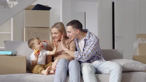 Happy Family Householders with Kid Sitting on Couch at New Home at Moving Day