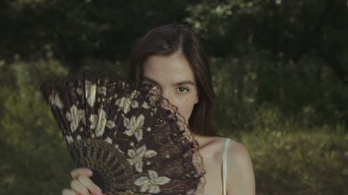 Portrait of Enigmatic Woman with Hand Fan Outdoors