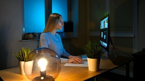 Thumbnail for Frau, die aufmerksam auf Computer in der Nacht