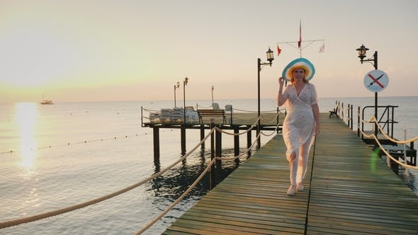 Thumbnail for A Woman in a Pair and Hat Walks on the Pier in the Early Morning. Breathes in the Fresh Air.