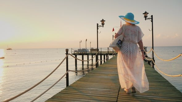 Thumbnail for A Woman in a Pair and Hat Walks on the Pier in the Early Morning