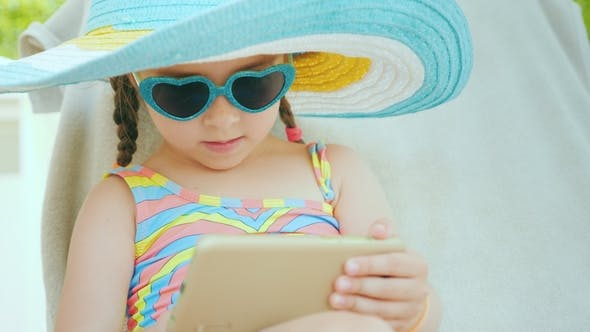 Cover Image for A Little Girl in a Swimsuit Resting on a Lounger, Using a Smartphone. Holiday with Children