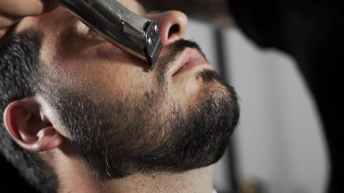 Tattoed Barber Shears the Customer's Mustage By Using Trimmer and Comb at the Barber Shop, Man's