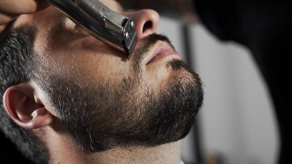 Thumbnail for Tattoed Barber Shears the Customer's Mustage By Using Trimmer and Comb at the Barber Shop, Man's