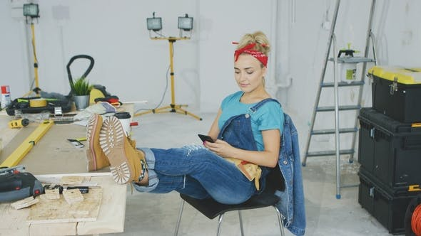 Thumbnail for Woman Resting with Smartphone at Carpenter Workbench