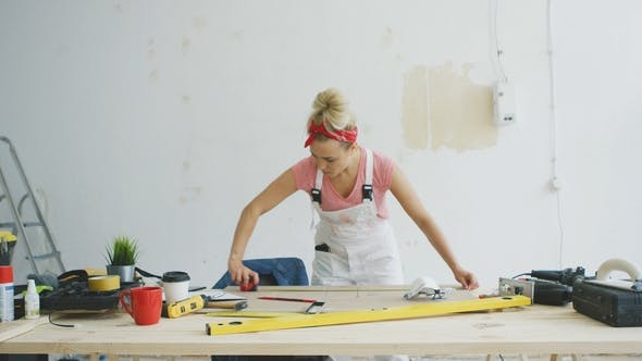 Thumbnail for Female Carpenter Measuring Wood on Workbench