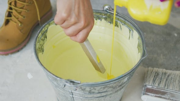 Thumbnail for Hand Mixing Yellow Wall Paint in Bucket