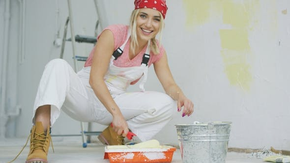 Thumbnail for Smiling Female Dipping Paint Roller in Tray