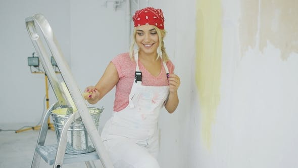 Cover Image for Happy Female Dipping Brush in Wall Paint