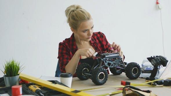 Thumbnail for Female Repairing Radio-controlled Car