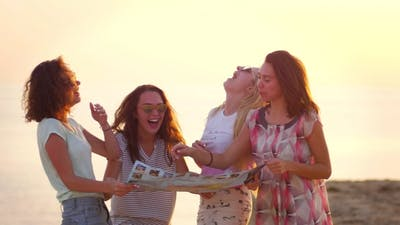 Women Laughing Together on Beach Sunset. Laughing People Traveling