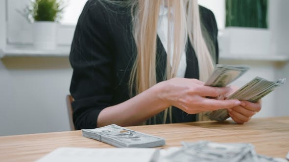 Business Woman Counting Cash in Hands