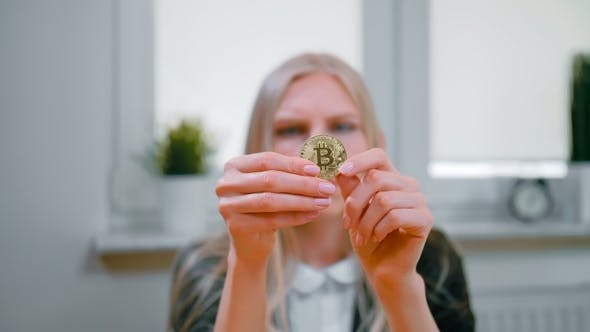Thumbnail for Woman Studying Bitcoin in Hands