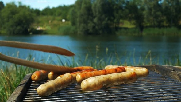 Thumbnail for Grilling Sausages on a Sunny Summer Day in Front of a Lake