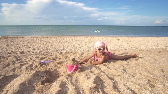 Thumbnail for Little Baby Girl In A Bathing Suit And Sunglasses On Playing Sandy Beach