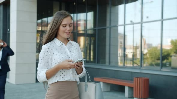 Dolly Shot of Ambitious Young Businesswoman Walking Along Modern Office Center Using Smartphone