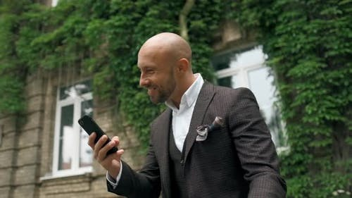 Success and Achievement - Happy Businessman Is Cheering Celebrating and Looking at Cell Phone. Young