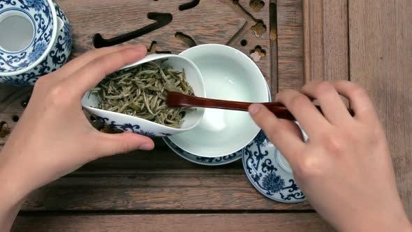Filling A Brown Teapot Through A Funnel