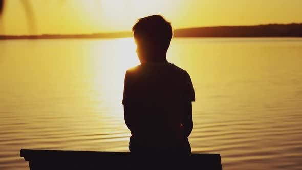 Thumbnail for Little Boy Sitting on Wooden Dock at Sunset
