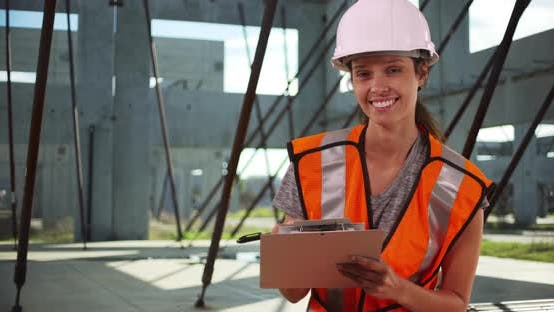 Thumbnail for Female construction worker using clipboard and smiling at camera on job site
