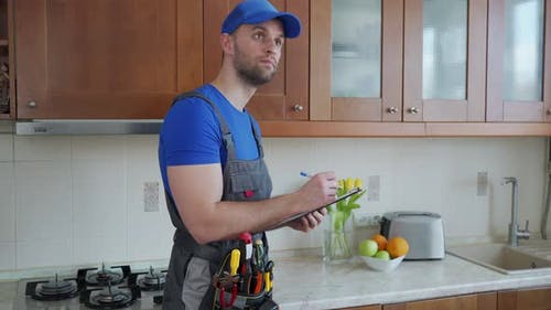 The Repairman Stands in the Kitchen in a Blue Cap and Writes in a Tablet