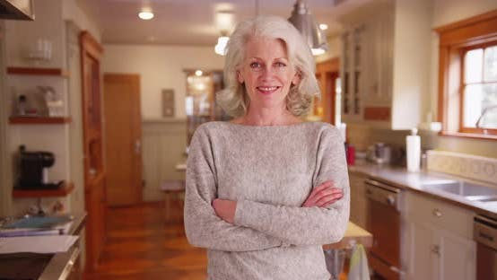 Thumbnail for Cheerful elder woman in grey sweater smiling at camera inside charming kitchen