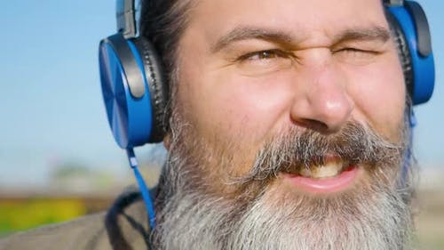 Bearded Middleaged Man with Headphones Listens to Music Sings Along and Nods to the Beat of the