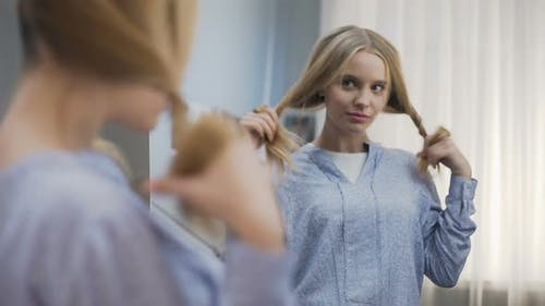 Pretty School Girl Trying Different Hairstyles in Mirror, Preparing for Party